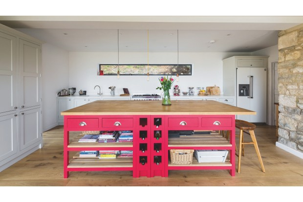 A hot pink island with wooden worktop takes centre stage in this kitchen by The Shaker Kitchen Company. Keep walls and fitted units neutral for balance.