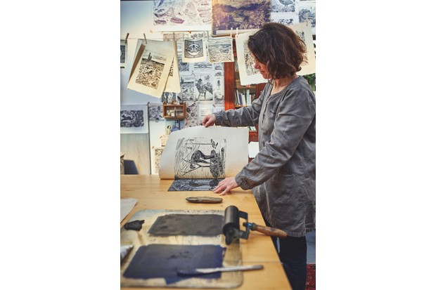 Lou Tonkin peels away paper from the Lino block to show a finished print