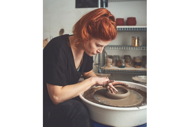 Sarah uses a wheel to create a mug shape, before 'turning' to refine.