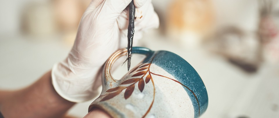 Sarah paints lustre onto a finished mug