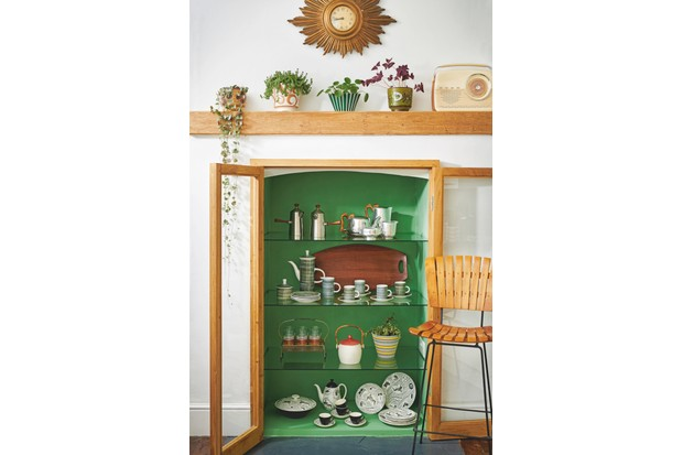 Zesty green cupboard displaying a striking collection of tea and coffee pots