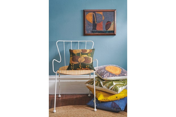 Vibrant oversized cushions styled beside a classic mid-century chair