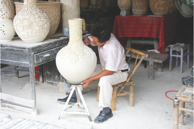 Adding detail to a large vase at a Jingdezhen ceramic museum