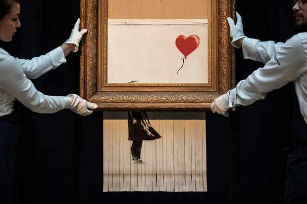 LONDON, ENGLAND - OCTOBER 12: Sotheby's employees pose with 'Love is in the Bin' by British artist Banksy during a media preview at Sotheby's auction house on October 12, 2018 in London, United Kingdom. During Sotheby's Contemporary Art Sale on 5th October the Banksy artwork 'Girl with Balloon' shredded through the bottom of the frame as it was sold. With Banksy being responsible for the shredding, the buyer has agreed to proceed with the sale and it is now titled 'Love is in the Bin' and said to be worth more than the £1.04million paid. (Photo by Jack Taylor/Getty Images)