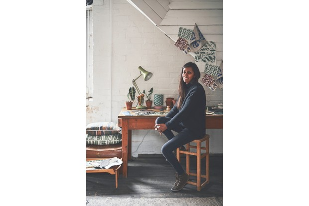 Artist Kiran Ravilious sitting at a vintage desk in her workshop