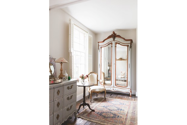 A delicate gilt chair is a perfect partner to this charming French armoire.