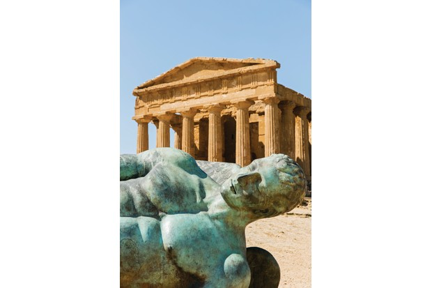 Bronze statue of Fallen Icarus resting in the foreground of a Greek Temple