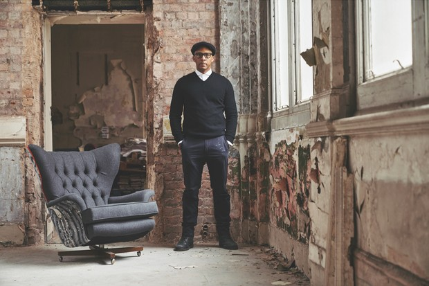 Portrait of Jay Blades in a warehouse alongside one of his re-upholstered vintage armchairs