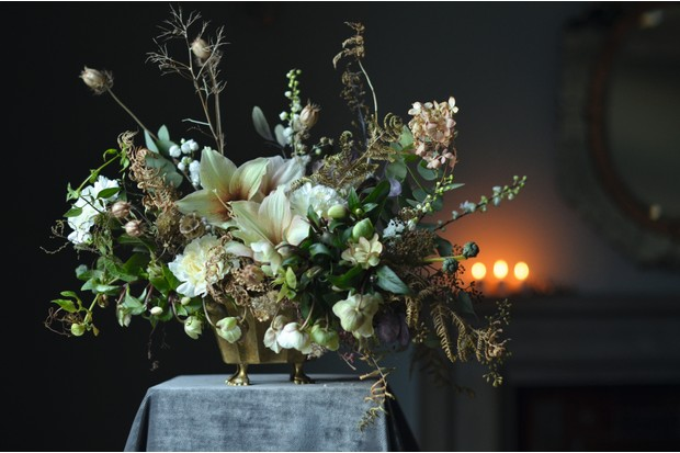 Antique brass bowl on feet filled with seasonal foliage and winter flowers including amaryllis and hellebores, £100, Simply By Arrangement.