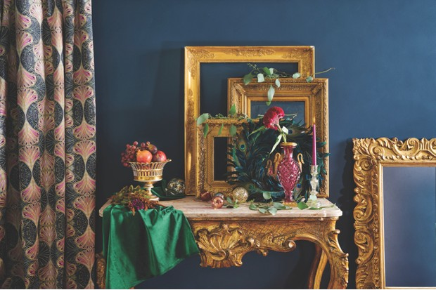 Hall table dressed with fresh foliage and ornate gilt frames