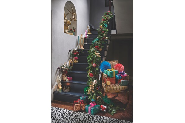 Staircase decorated with swags of greenery and oversized baubles