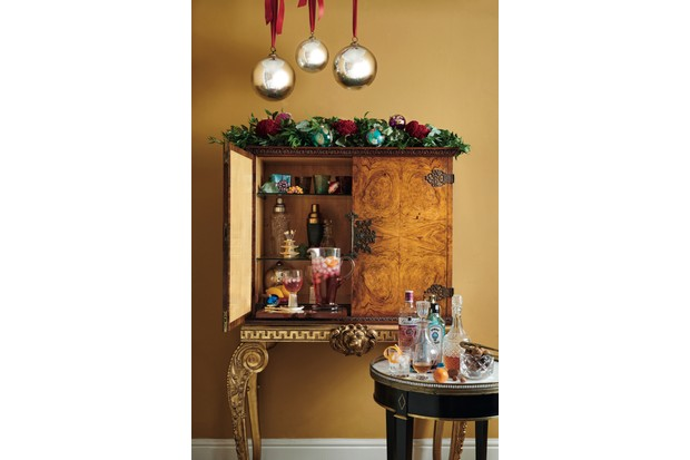 Drinks cabinet decorated with fresh greenery, a selection of artfully placed ornaments and a clutch of witch balls for a super-sized statement.