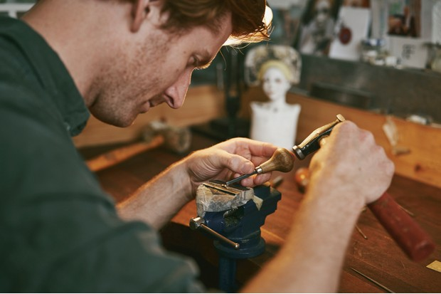 Samuel works on a piece of jewellery in his vice