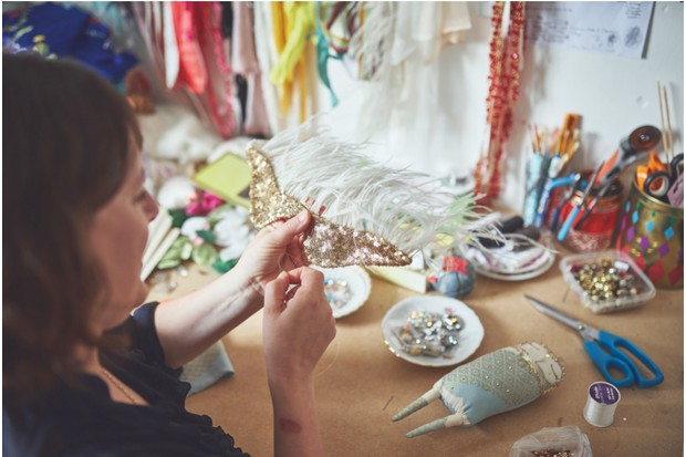 Alice sewing gold sequins onto one of her enchanting doll designs