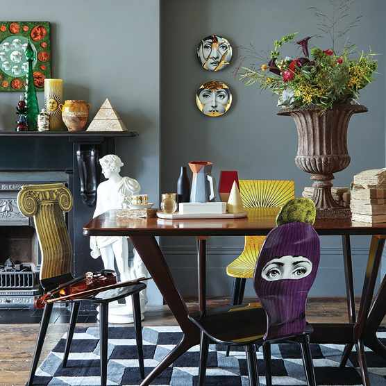 Fornasetti's whimsical designs – many based on trompe l'oeil effects – turn a potentially formal dining area into a playful and witty space. Photo: Katya de Grunwald
