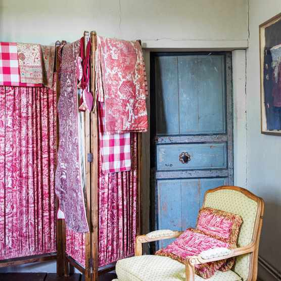 Lengths of antique toile de Jouy made into decorative screens in a bedroom