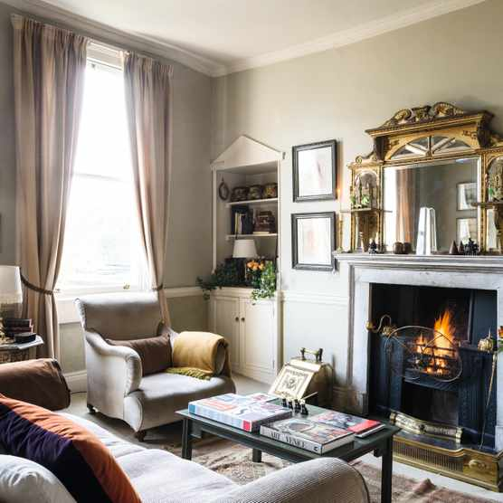 The sitting room features an overmantel mirror that the couple bought at an auction in Plymouth. The inherited club chair has a throw from the Biggest Blanket Company. An Edwardian brass coal box and fender complements the unusual Regency fire guard