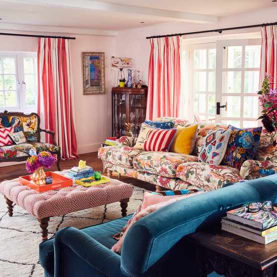 Sophie Robinson's living room demonstrates her approach to scale when using colour and pattern. One sofa features the dominant floral fabric, which contrasts with the glorious candy-stripe curtains.