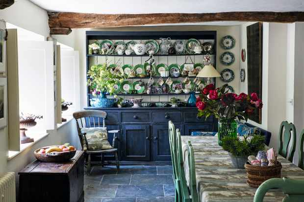 A countryside dining room featuring a Welsh dresser filled with antique ceramics