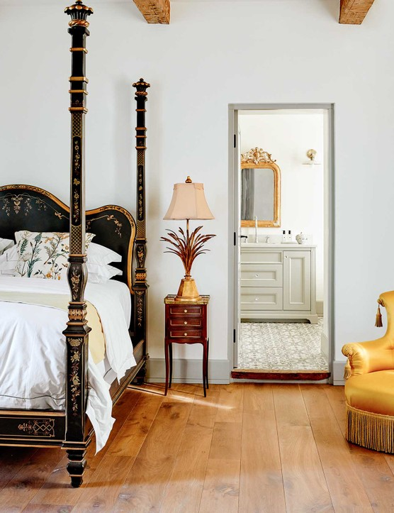 Although the decor is deliberately neutral, Michelle has taken care to ensure that each bedroom has its own personality. Here, textiles and prints create a bucolic theme. The hand-coloured botanical prints on the wall are early 19th-century. The painted bed with its butterflies and flowers was the inspiration for the room.