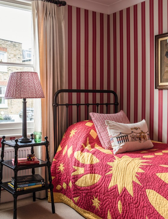 The 1920s bed in Sophie and Henry's son's bedroom has been reconditioned and given a bronze finish. The ebonised bobbin side table came from Jamb and the bronze lamp is antique and has a lampshade from Fermoie. A bold red and yellow quilt, in combination with a smart striped wallpaper from William Yeoward, gives the room a vibrant feel