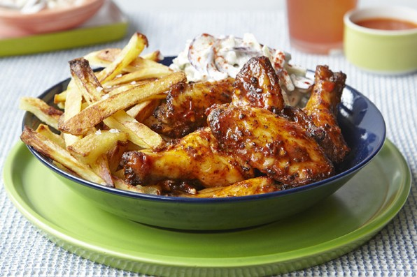 A blue bowl filled with chicken wings and golden fries