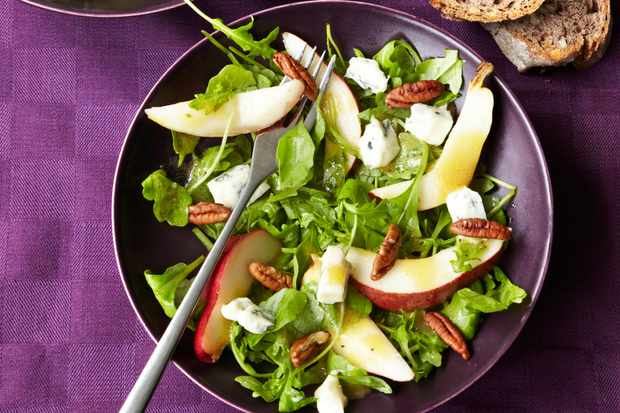 Pear Salad Recipe with Pecans and Blue Cheese served in blue dishes on a purple table cloth and brown bread on the side