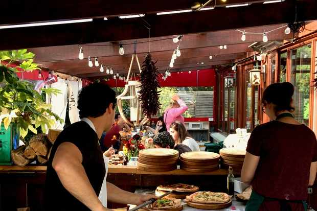 The inside of a small restaurant with a man and a woman cooking pizzas