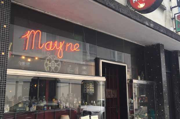 A shop front has black tiles and a glass window. In the window is a red lit sign reading 'mayne'