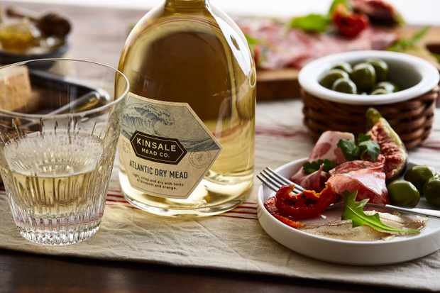 A wooden table is laid with a glass bottle of mead, a small glass and a plate topped with olives and cured meats