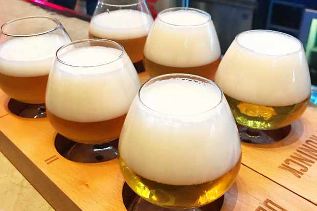 6 short beer glasses on a wooden board