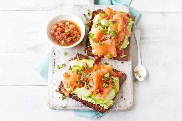 2 pieces of toast topped with avocado and smoked salmon, with a pot of salsa