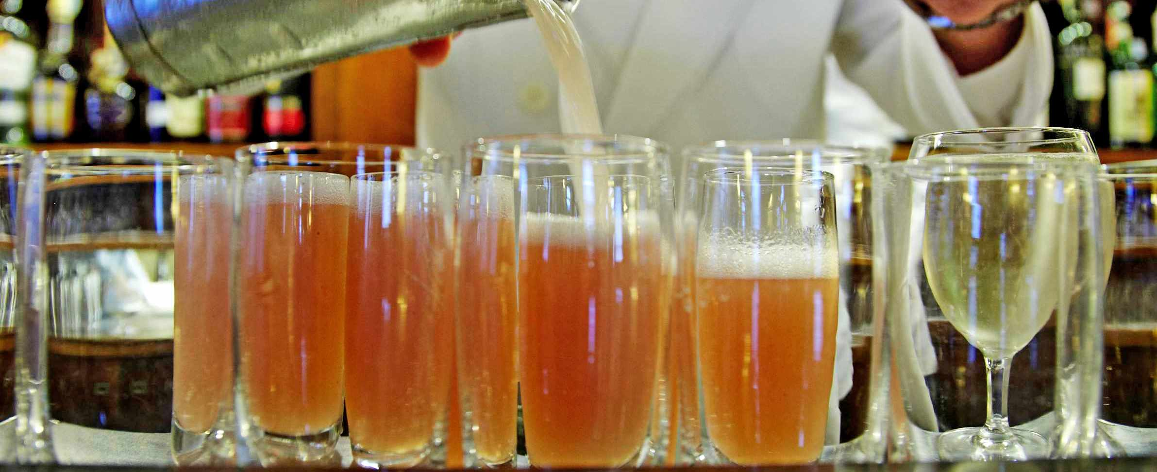 Waiter pouring orange bellinis into flutes