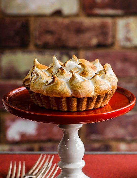 A red cake stand is topped with a golden pastry tart with piped meringue on top
