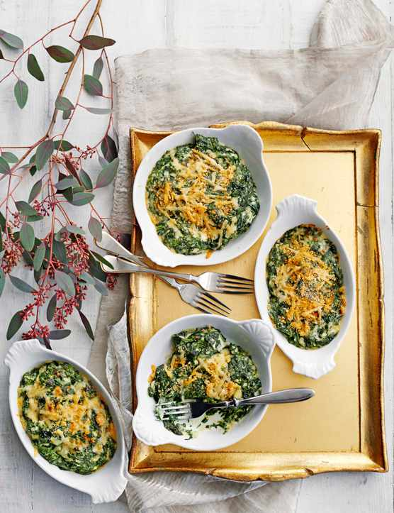 Three white bowls filled with a green spinach gratin with melted cheese on top