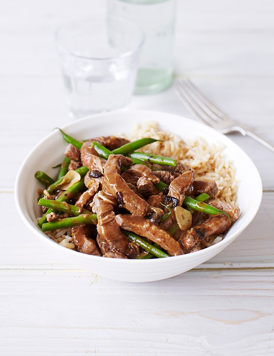 Big white bowl of Beef and Black Bean Stir-Fry with a silver fork