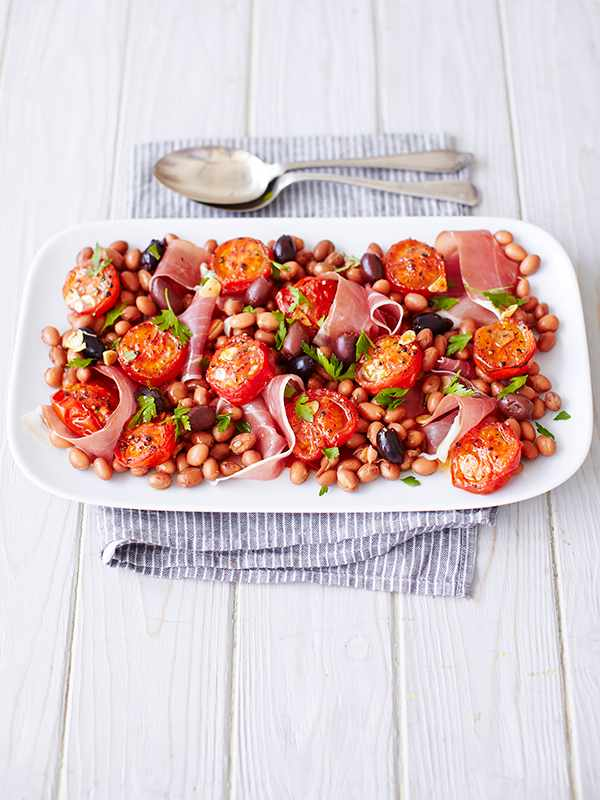Tomato Salad Recipe with Prosciutto and Borlotti served on a long white late with a thin stripy blue and white cloth