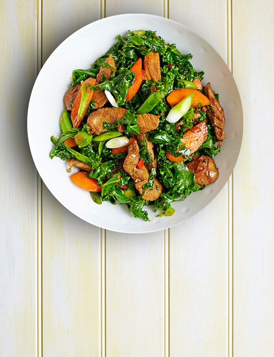 Pork Stir-Fry Recipe with Spring Onions and Kale served in a round white bowl on a light wooden table