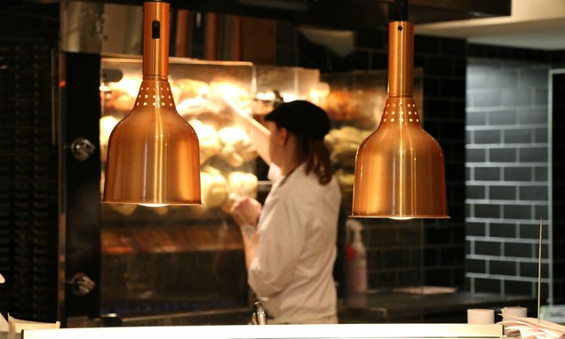 A chef staffing the roasting spit at Reys, Cambridge with metallic lights in the foreground