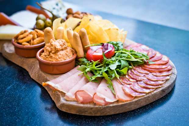 A wooden board topped with cold meats, dips and cheeses
