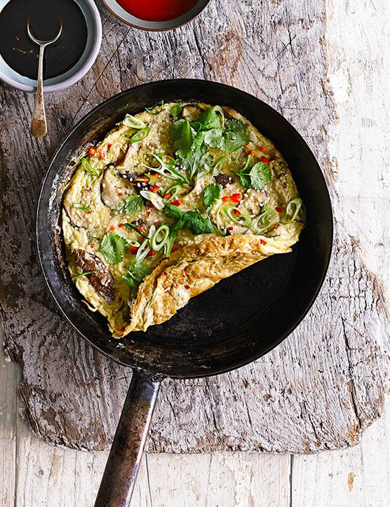 Mushroom Omelette Recipe with Ginger and Spring Onions served in a black frying pan on a wooden board