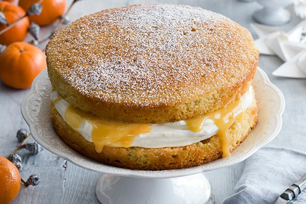 Victoria Sponge Recipe with Spiced Christmas Curd on a white cake stand and christmas background