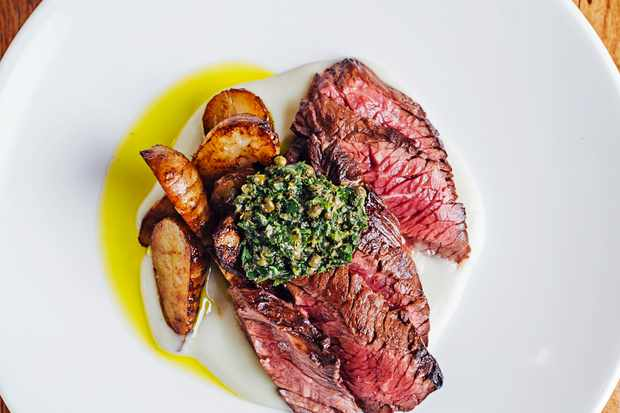 A white plate topped with pink steak, potatoes and green sauce