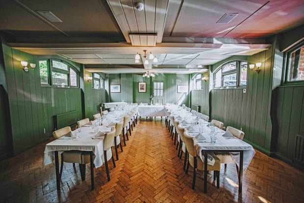 A large dining room with green walls and wooden parquet flooring