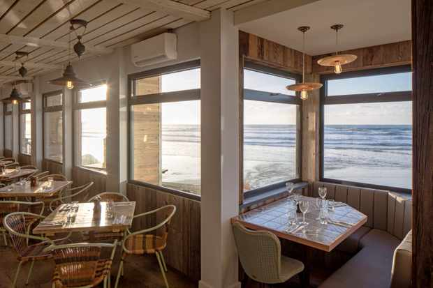 A corner dining room with wooden tables and chairs and windows looking out to sea