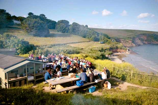 People are sat on picnic benches looking out over green fields and the sea