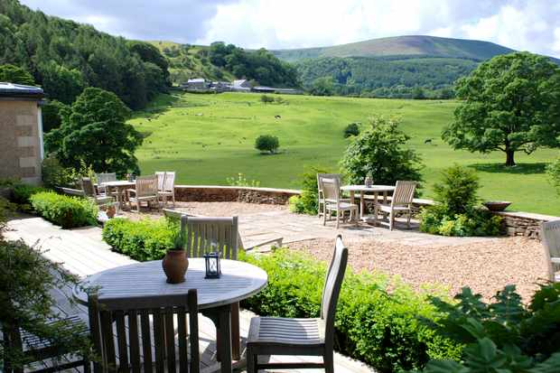 A pretty garden with tables and chairs looking out over green fields