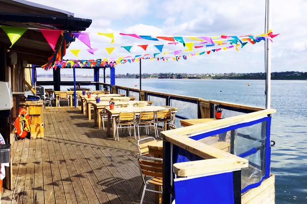 A decked area with tables and chairs perched over the sea with colourful bunting hanging overhead