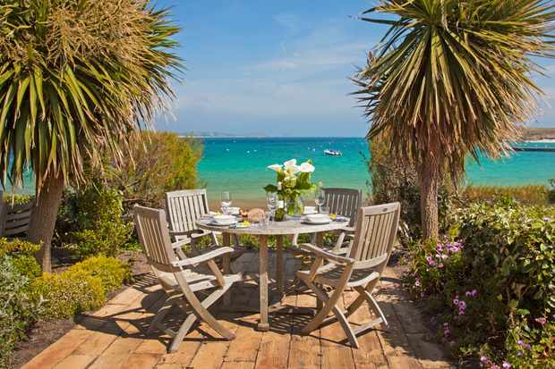A wooden table and chair on decking looking out to sea