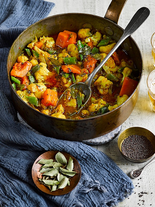 Pan of vegetarian curry with black pepper on the side